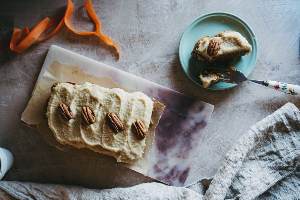Korenčkov kolač s kremo iz indijskih oreščkov.