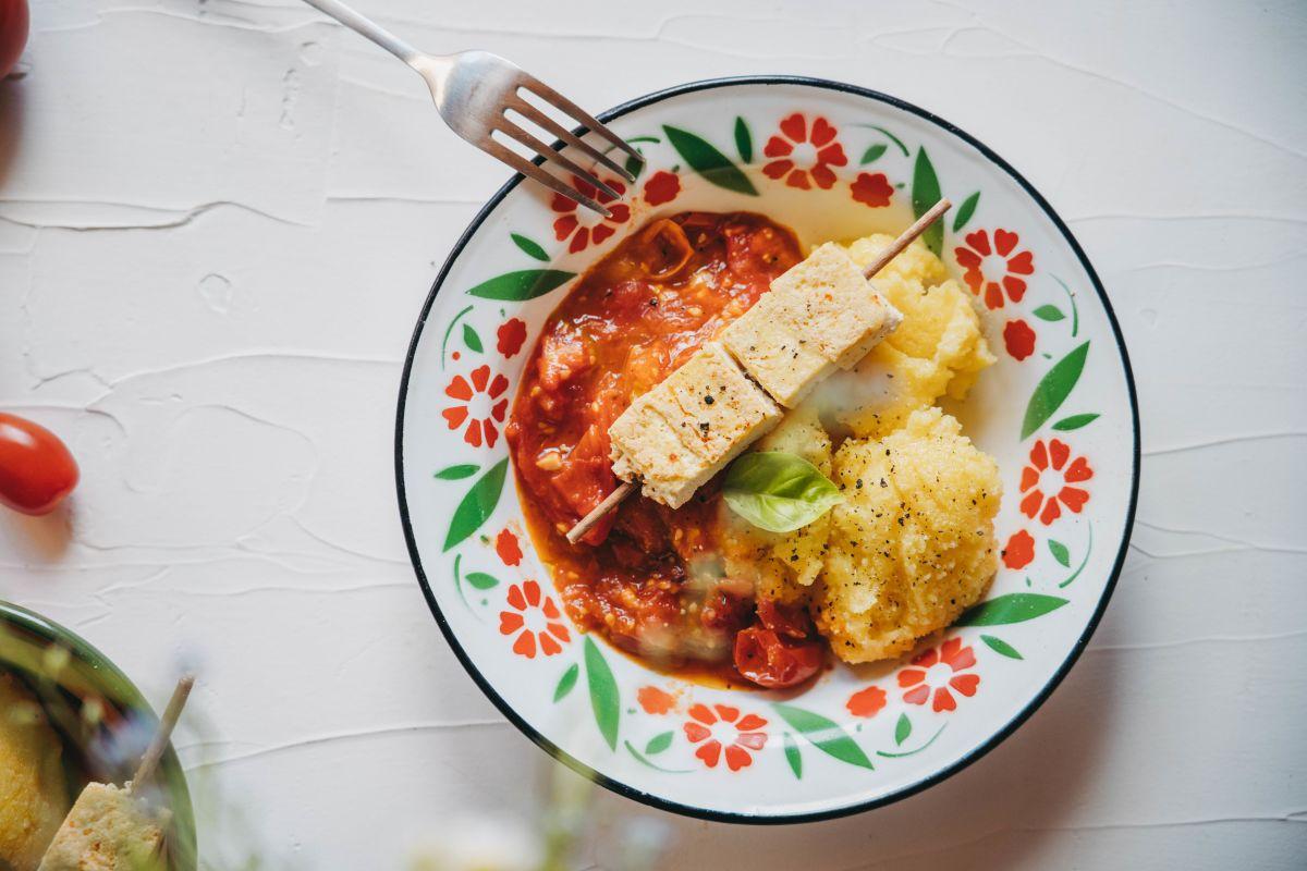 Kremna polenta in paradižnikova omaka servirana skupaj z vegi ražnjiči.