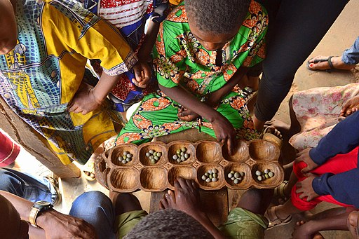 Children gather over a game of Ayo