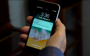 rentredi subscription: man's hand holding an iphone that shows a notification for rentredi landlord-tenant software