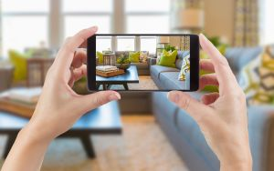 real estate marketing 2021: Female Hands Holding Smart Phone Displaying Photo of House Interior Living Room Behind.