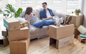 inherited tenants image: image of a young female and male sitting on a couch surrounded by moving boxes and chatting