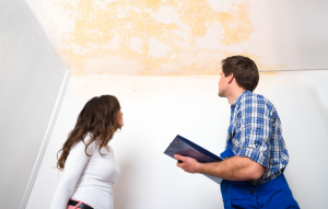 inspecting occupied properties image: woman and man with clipboard staring at water stain on white ceiling