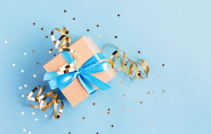 tenant gift-giving image: picture of a presents wrapped with brown wrapping paper and blue ribbon and gold confetti