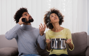 property management image: young couple staring at ceiling with water leaking; the man is on the phone while the woman holds a pot to catch the water leaking