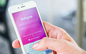instagram screening tenants image of a hand holding a phone with the instagram app open