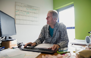 manage your rentals remotely image: picture of a 60-year old man in a flannel shirt working on the computer sitting at his desk