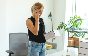 virtual viewings: picture of a blond woman with a ponytail and a black shirt talking on the phone and holding a box