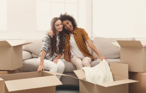 Can i afford to move out? header image: two roommates hugging and smiling over boxes