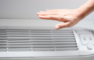 how to stay cool in summer header image: woman's hand over an AC unit to check if it is blowing cool air