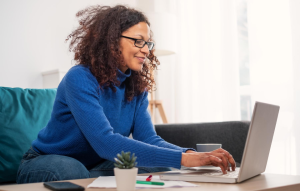 marketing your property management business header image: woman with glasses and long sleeve blue sweater smiling at laptop