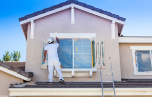 ultimate guide to house flipping header image: man in white shirt and pants painting tan house