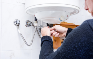 plumbing myths image: man's hand fixing sink