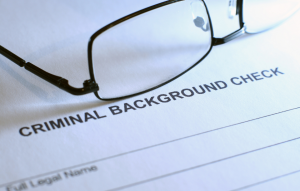tenant background checks image: picture of glasses sitting on top of a paper that says criminal background check