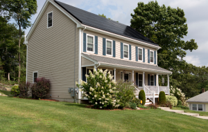 long-term rental property image of yellow house with front porch and green grass with a lilac bush