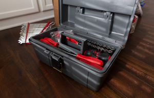 property safety tips: black toolbox with red tools on hardwood floor