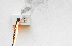 holiday electrical accidents: cord plugged into socket on fire