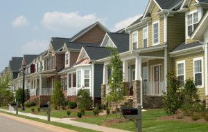 loans for real estate investors image of colorful houses along a neatly trimmed street