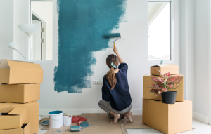 best paint color: image of a woman painting a room deep turquoise blue with a paint roller