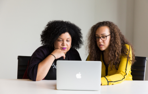 header image for property maintenance service: two women researching on a laptop