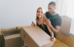 rental improvement ideas for landlords image: young, smiling couple with moving boxes