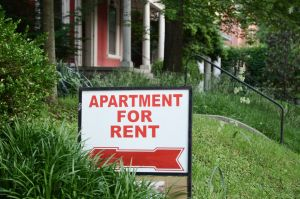 "ultimate guide to rental property management software: ""apartment for rent"" sign next to a green bush"