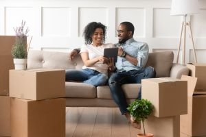 image of young couple sitting on couch surrounded by moving boxes signing electronic leases on their ipad