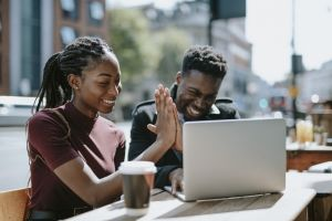 best states to buy rental property hero image of young couple high fiving each other in front of laptop