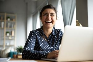 rentredi referral program hero image of smiling woman looking over laptop at camera