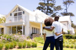 how to avoid rental scams hero image: picture of a young couple standing in front of a cute home
