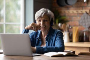 switch to rentredi hero image: older woman wearing headphones and smiling at laptop