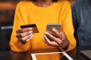 why landlords shouldn't use venmo for rent image: Close-up of a young woman in cafeteria using mobile phone and credit card for shopping online