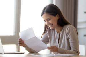free landlord reference letter template hero image: smiling woman holding a piece of paper & excited