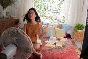 keep a room cool without ac hero image: young woman sitting in bed in front of fan