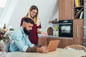 schedule a rentredi demo hero image: young couple looking at laptop together in their kitchen