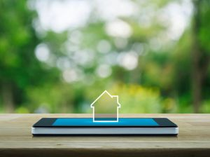 real estate investing strategies hero image of a house icon positioned on top of a smartphone