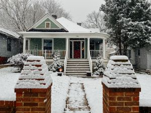 prepare rental for winter: snow covered house with a snowy walkway