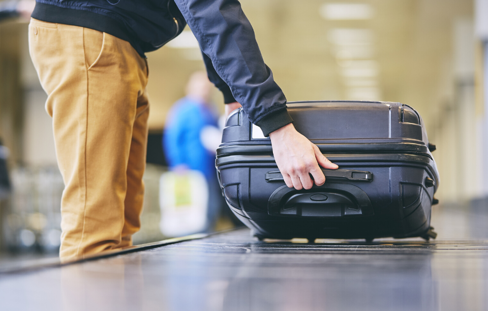 property management app image: man wearing khaki pants and long black sleeve shirt picking a black hardshell suitcase up off an airport turnstile