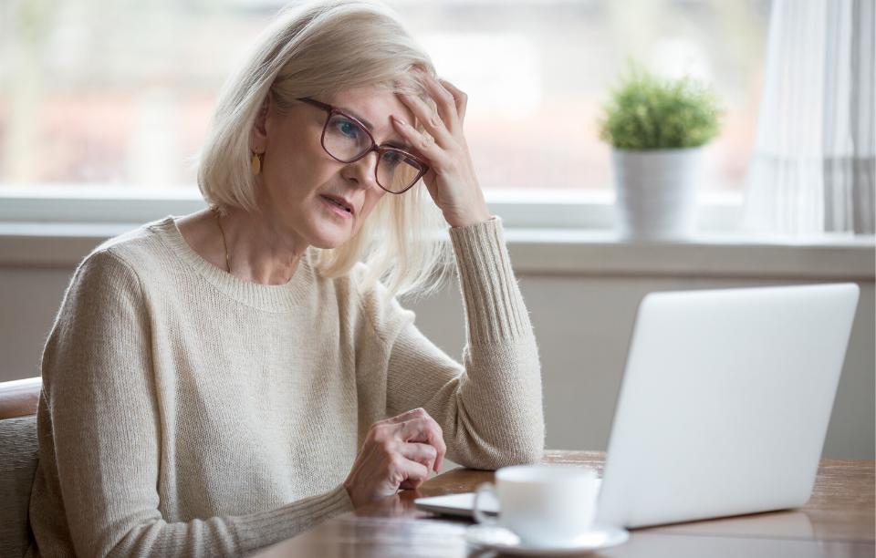 landlord pain points image: image of a woman with gray hair and glasses staring frustratedly at a screen with her hand on her head
