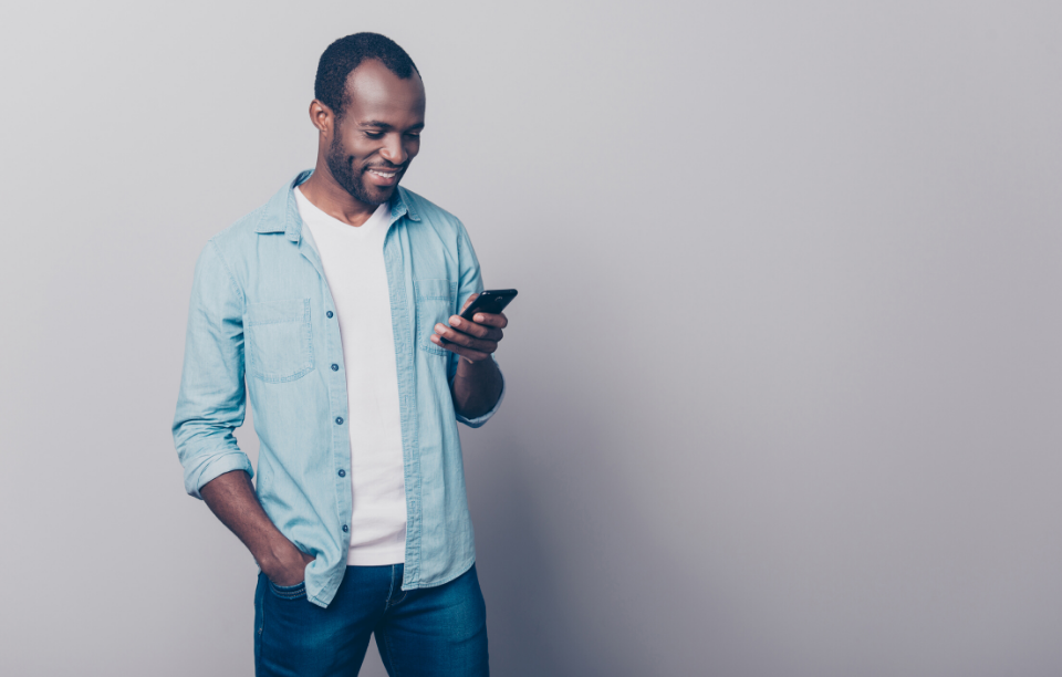 managing maintenance requests with video image: man wearing denim shirt smiling at phone in front of a grey wall