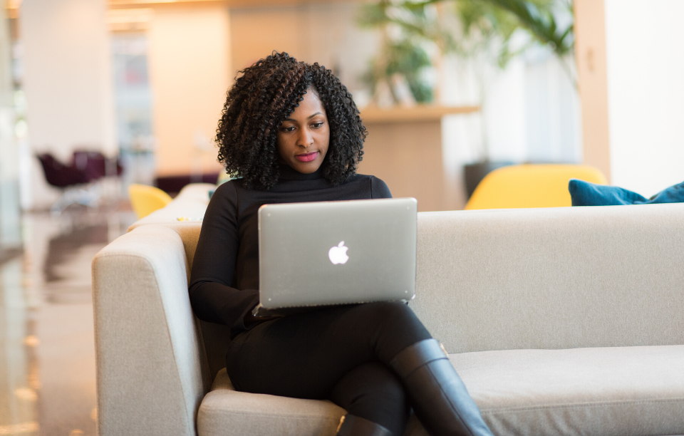 manage your rentals remotely image: a woman dressed in all black sitting on a couch working on a macbook laptop