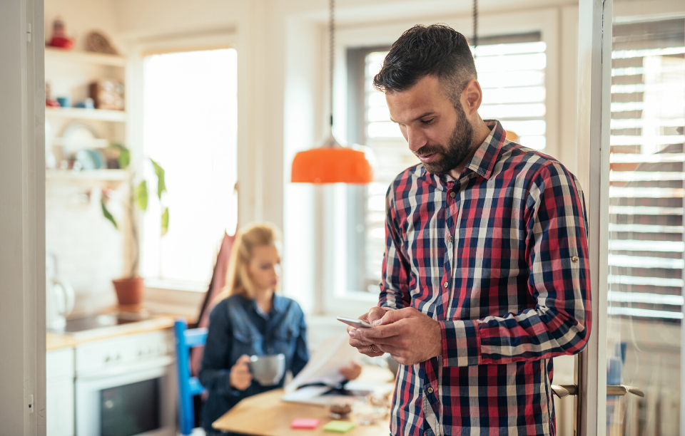 mobile rent payments image: picture of a well-groomed man wearing flannel on his mobile phone, blond woman drinking coffee and reading newspaper in the background