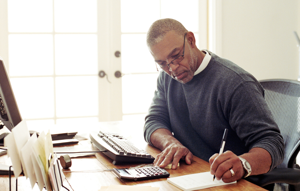older man with glasses writing on a piece of paper at home desk managing your properties from home
