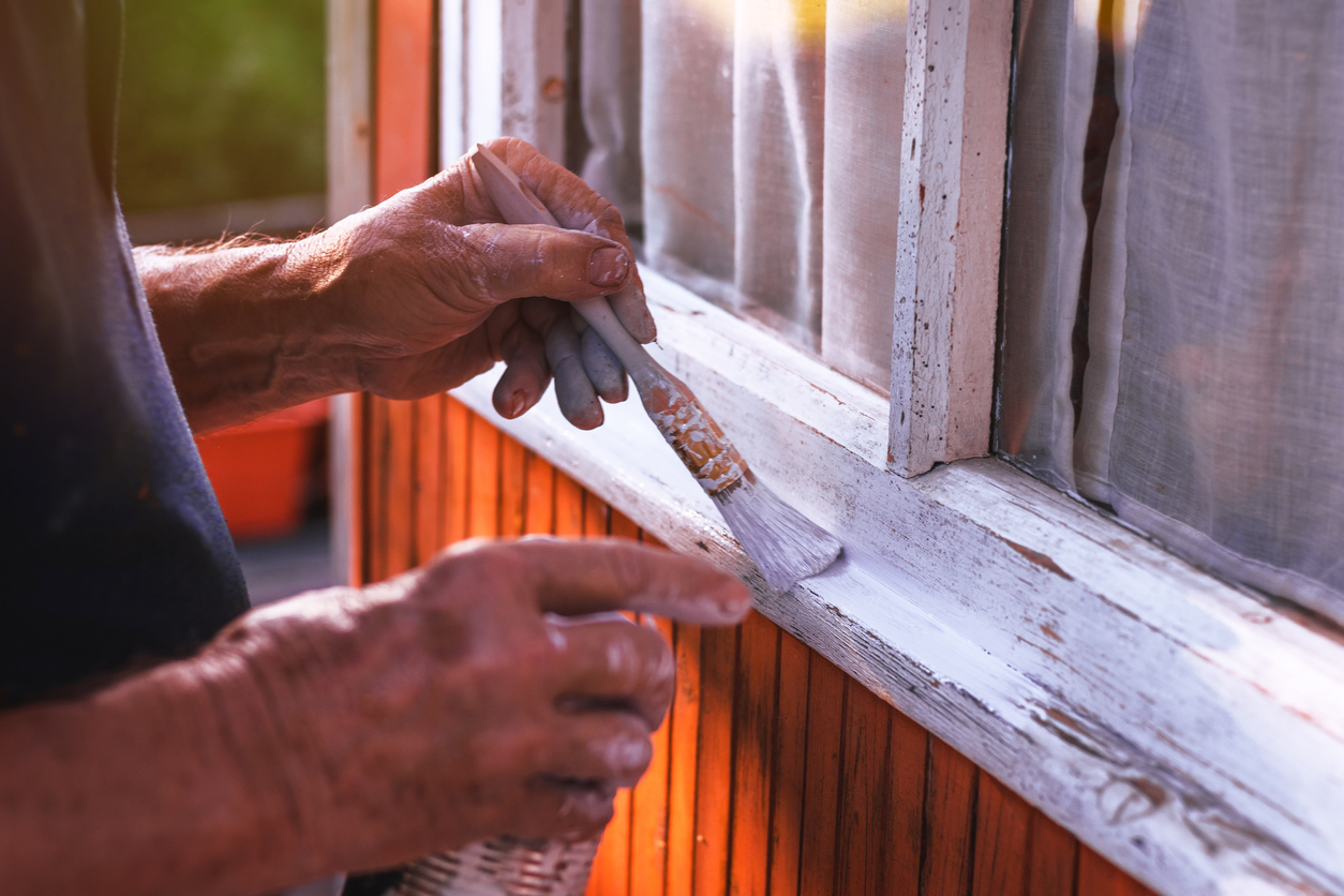 senior man painting white window sill for summer DIY project