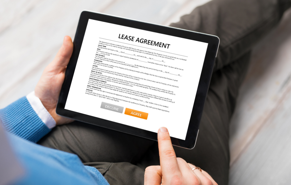 best lengths for leases image: person wearing blue long sleeve sweater and dark grey slacks holding an ipad with a lease agreement displayed