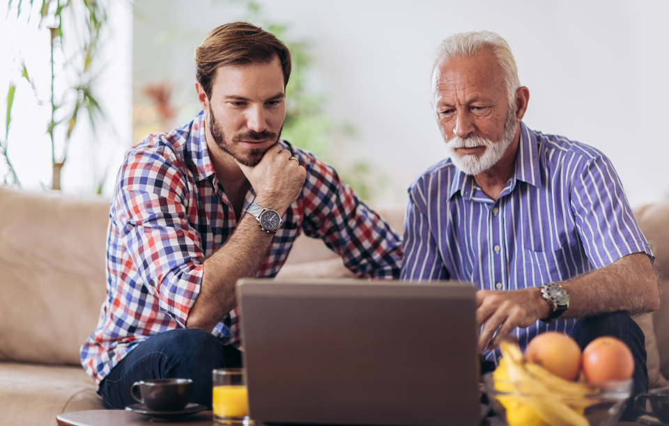 rentredi vs buildium header image: a mid-age man and an older man looking thoughtfully at a laptop