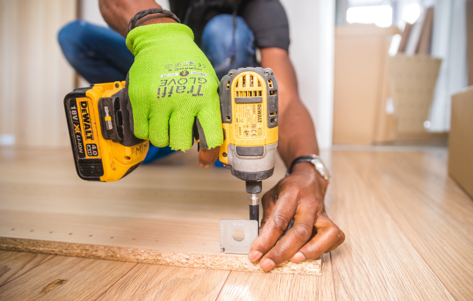 house flipping tip header image: man's hand drilling a wood board into the floor