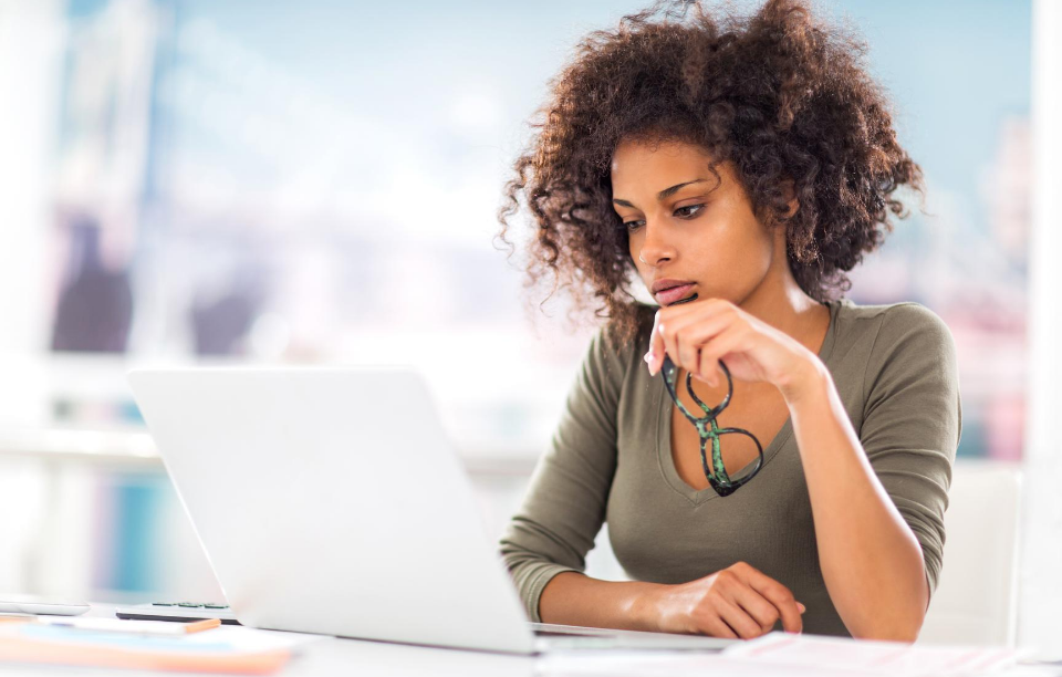 tenants with bad credit header image: woman staring at laptop holding her glasses in hand and slightly frowning thoughtfully at her computer