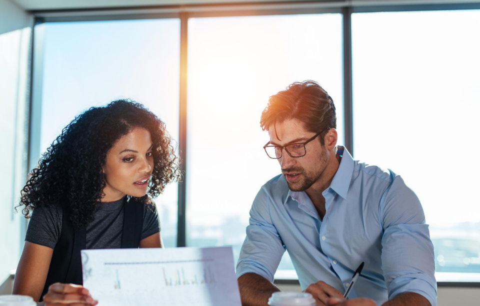 increase your ROI with landlord-tenant software header image: woman and man in their 30s looking at a document together with the sun shining in the office window