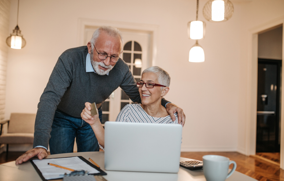 rental business organized header image: older couple working together on laptop and smiling